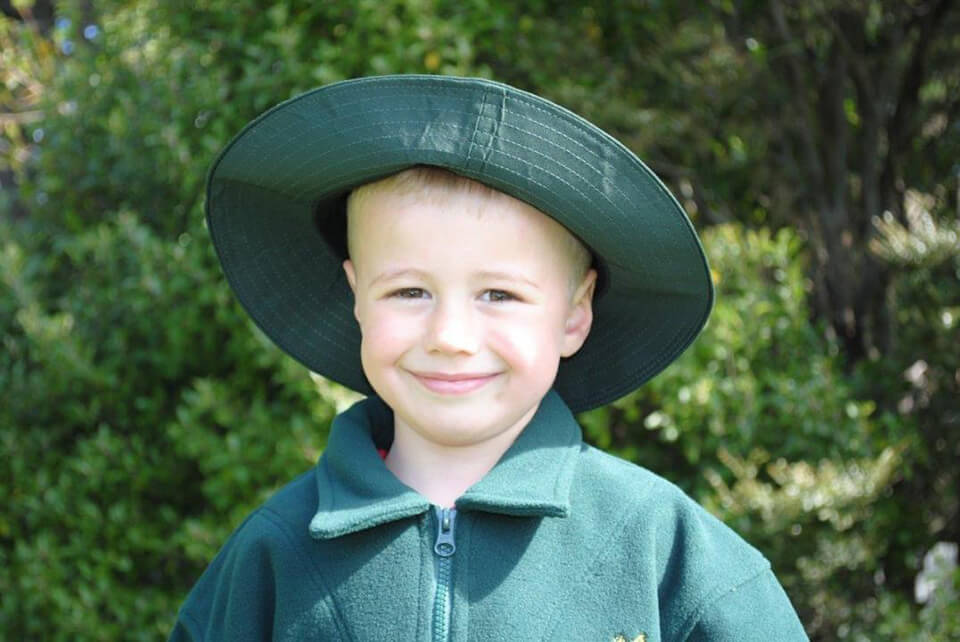 Te Anau School Child wearing a green hat as part of uniform